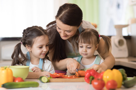 Mom chopping vegetables with kids daughters in a family home kitchen.
