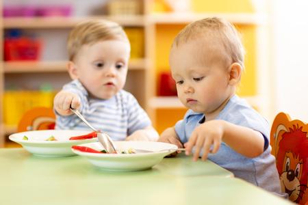 Foto de babies children boys eating healthy food in nursery or kindergarten - Imagen libre de derechos