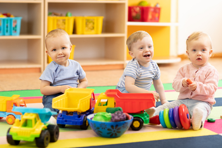 Foto de Group of babies is playing on floor in nursery or creche. Children in the day care center. Fun in the children's playroom - Imagen libre de derechos