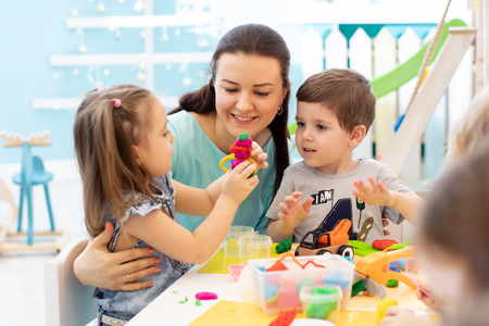 Photo pour Teacher with children working with plasticine at kindergarten or playschool - image libre de droit