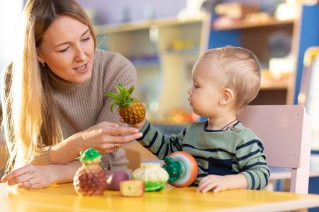 Photo pour Cute nursery teacher with child toddler boy playing educational toys in kindergarten - image libre de droit
