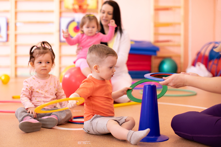 Foto de Nursery kids group doing sport in gym - Imagen libre de derechos