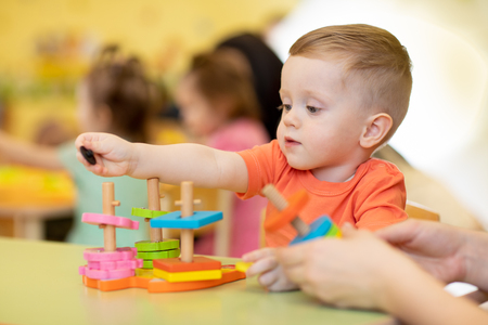 Photo pour Child boy together with teacher playing educational toys at sunny day in nursery - image libre de droit