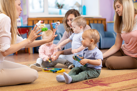 Photo pour Mothers and their children together in club. Babies play with musical toys - image libre de droit