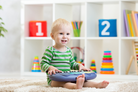 Photo pour Kid boy playing toy piano in nursery - image libre de droit