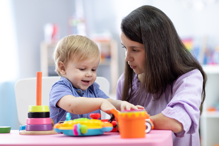 Photo for Cute woman with child playing with plastic blocks at home or kindergarten - Royalty Free Image