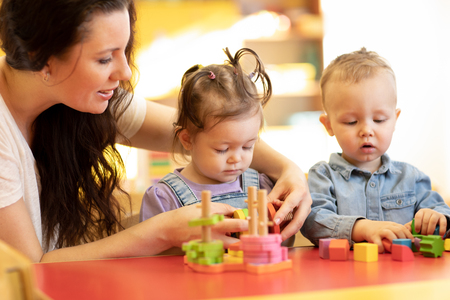 Photo pour Children play with shapes and colorful wooden puzzle in a montessori classroom - image libre de droit