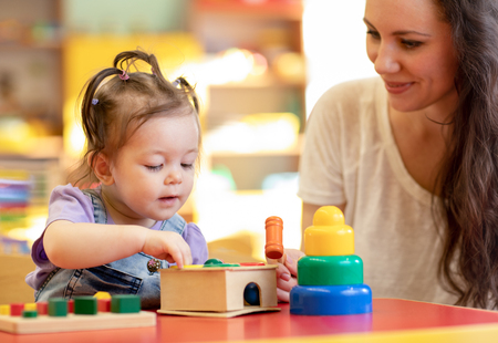 Photo for Nursery kid playing developmental toys with mother or teacher - Royalty Free Image