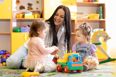 Photo pour Nursery children playing with teacher in kindergarten - image libre de droit