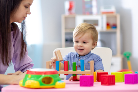 Photo pour Nursery baby and caregiver play at table in daycare centre - image libre de droit