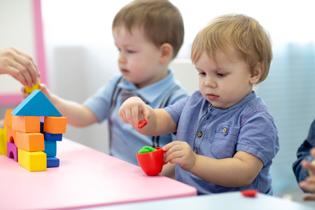 Photo pour Children toddlers play colorful clay toy in kindergarten - image libre de droit