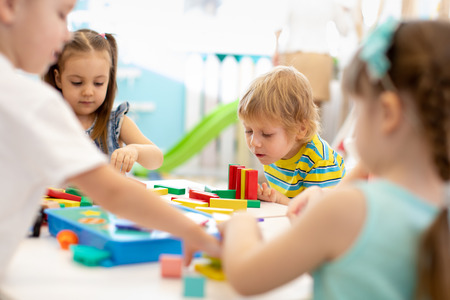 Photo pour Group of kindergarten kids at day care. Happy children playing with plastic building blocks at kindergarten - image libre de droit