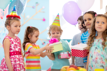 Photo pour Childhood, holidays, celebration and friendship concept. Happy children in party hats giving gifts at birthday party - image libre de droit