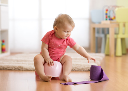 Photo pour Happy one year old baby girl sitting on chamber pot - image libre de droit