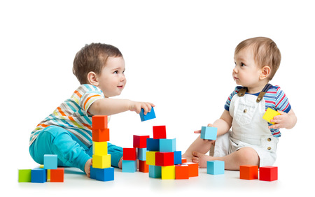 Photo pour Two kids building block towers. Isolated on white background - image libre de droit