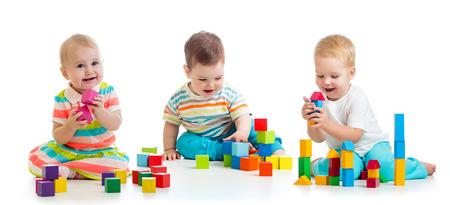 Photo pour Cute babies toddlers playing with toys or blocks and having fun while sitting on floor isolated over white background - image libre de droit