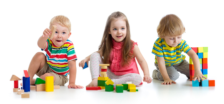 Photo pour Cute little children playing with toys or blocks and having fun while sitting on floor isolated over white background - image libre de droit