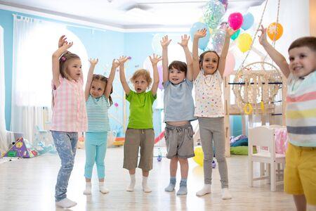 Photo pour Happy kids with hands up at daycare - image libre de droit