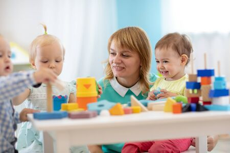 Photo pour Nursery children playing with teacher in the classroom - image libre de droit
