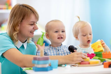 Photo pour Kindergarten babies together with teacher playeducational toys at sunny day in nursery - image libre de droit