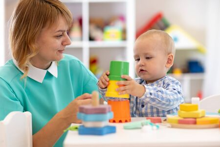 Photo pour Baby with mother in nursery at home. Child with teacher playing with educational cup toys in daycare or creche - image libre de droit