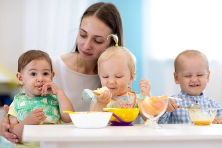 Foto de Group of nursery babies eat healthy food with kindergartener help. Lunch break in creche. Little children have dinner in daycare - Imagen libre de derechos