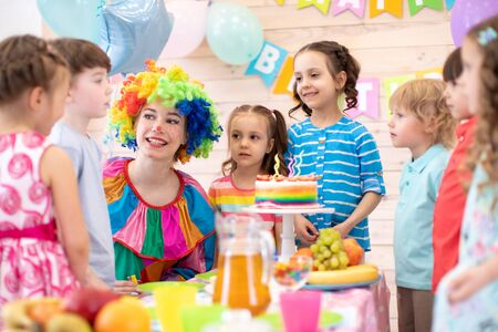 Foto de Clown playing with children. Kids group celebrate birthday at table. Holiday in a childrens club. - Imagen libre de derechos