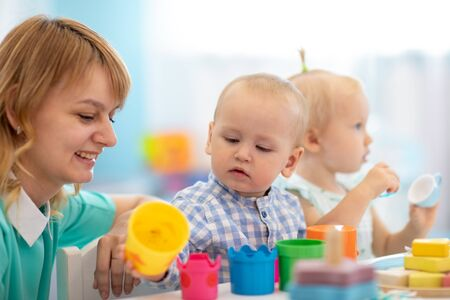 Photo for Smart babies in day care. Group of kids playing toys with kindergarten teacher. Children lesson in creche - Royalty Free Image