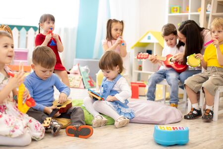 Foto de Kindergarten teacher with children on music lesson in day care. Little kids toddlers play together with developmental toys. - Imagen libre de derechos