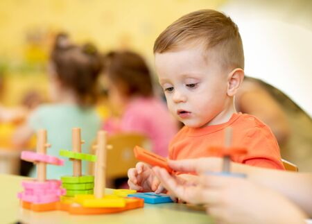 Foto de Little boy playing with educational toy in creche or nursery - Imagen libre de derechos