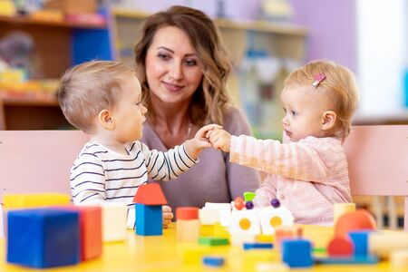 Photo pour Little caucasian babies playing with Montessori toy in pre-school, creche or kindergarten - image libre de droit