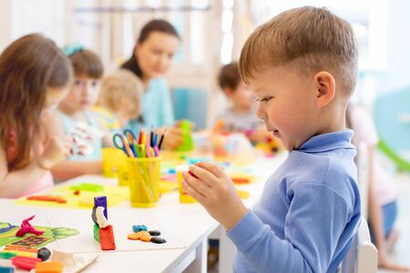 Foto de Child boy and group of kids working with colorful clay toy in nursery. Creative child molding in kindergarten. Preschoolers play with plasticine or dough. - Imagen libre de derechos