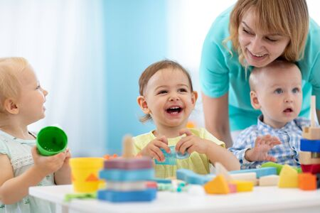 Photo pour Babies play with teacher in nursery - image libre de droit