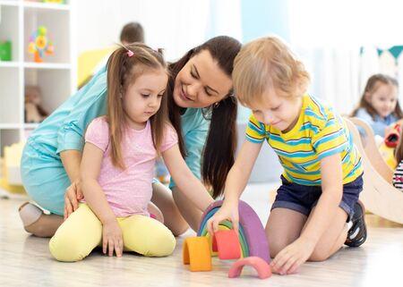Photo pour Preschool children and kindergarten teacher playing with wooden toys - image libre de droit
