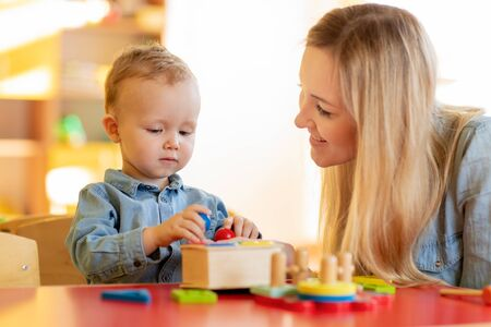Photo pour Woman and kid toddler playing logical toys at home or daycare center - image libre de droit