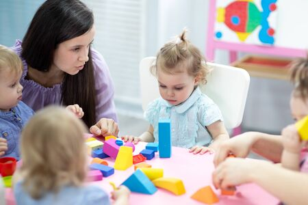 Photo pour Kids toddlers playing with color blocks on lesson in classroom in kindergarten - image libre de droit