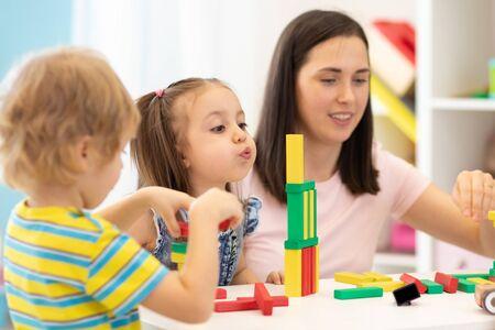 Photo pour Kids with teacher in kindergarten - image libre de droit