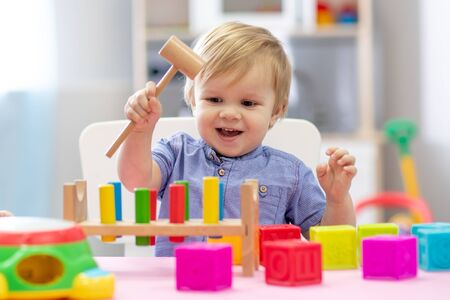 Photo pour cute toddler baby playing with wooden hammer block toy - image libre de droit