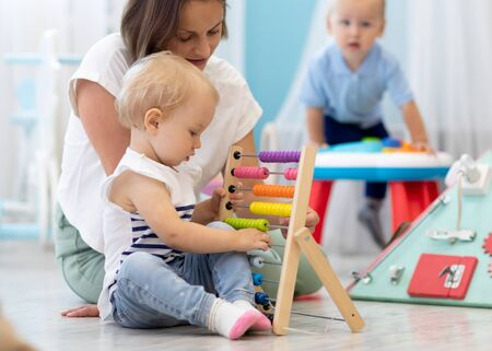 Photo pour Kids playing on floor with educational toys in kindergarten. Children have fun in nursery or daycare. Babies with teacher in creche - image libre de droit