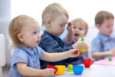 Foto de kids group playing with play clay at nursery or kindergarten or daycare - Imagen libre de derechos