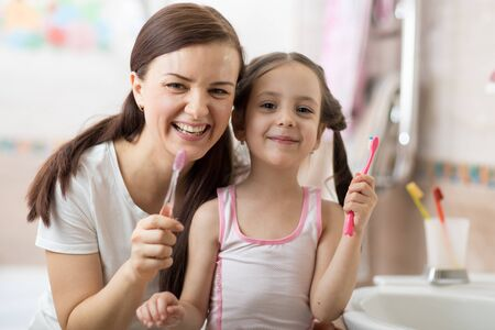 Foto per Smiling child kid with her mom brushing and clean teeth in bathroom - Immagine Royalty Free