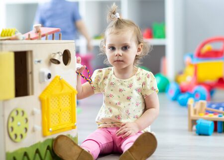 Photo pour Cute toddler baby playing with busy board in daycare. Childrens educational toys. - image libre de droit