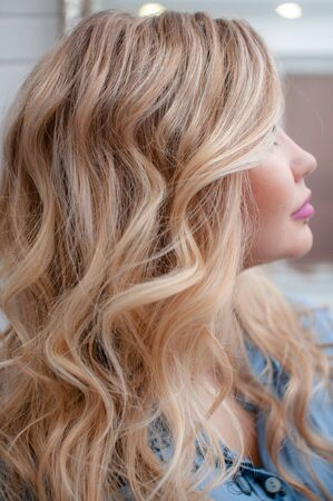 Photo for Portrait of a blonde girl with long curly hair in profile at a beauty salon - Royalty Free Image