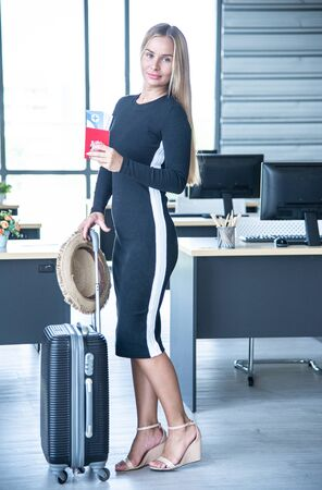 Tourist concept, Caucasian beautiful business woman with blue eyes, blonde long hair and leg hold the passport, air ticket, luggage and hat in the office prepare travel accessories for travelling in summer holiday