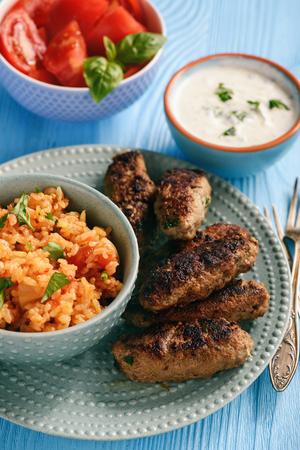 Photo pour Cevapcici, balkanian grilled meat sausages with savory rice and yogurt dip. - image libre de droit