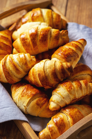 Foto de Homemade butter croissants on wooden tray. - Imagen libre de derechos