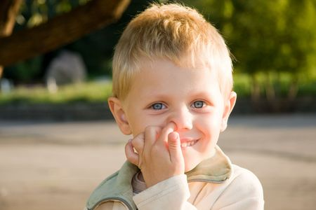 Three years old boy picking his nose outdoors