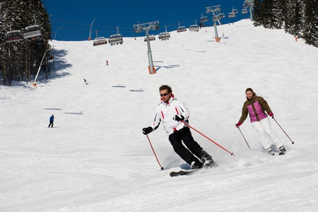 Man and woman downhill skiing on wide piste in alps mountains