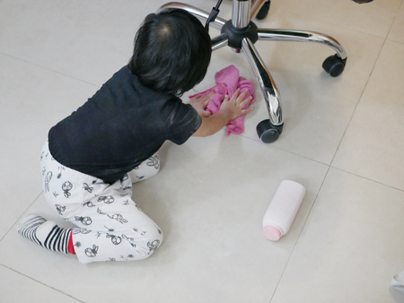 Little Asian baby girl cleaning her own mess, body powder, on the house floor - allowing baby to clean up their own mess to develop their sense of responsibility
