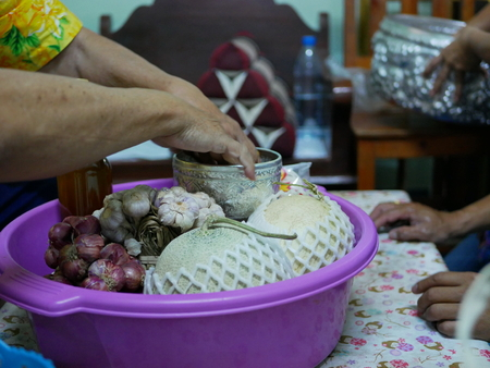 Selective focus of Thailand's local seasonal crops: melons, garlics, shallots, and honey being presented along with holy turmeric water to elderly people for paying respect to them during Songkran festival - Rod Nam Dam Hua ceremony